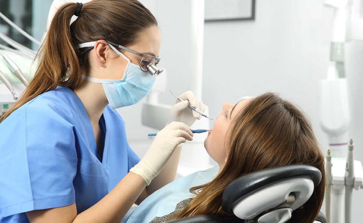 врач делает профессиональную чистку зубов